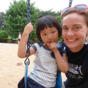 KKOOM Volunteer Christina (right) with a child