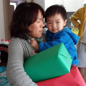 A toddler from Samsungwon gets his presents with the help of his house mom