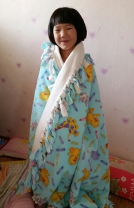A child at a Korean orphanage and her Joy for Kids blanket!