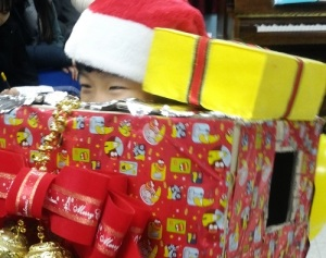 A child dresses up as a Christmas present at the Samsungwon party yesterday