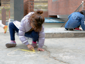 A child at Samsungwon plays with chalk on the Sunday volunteer visit